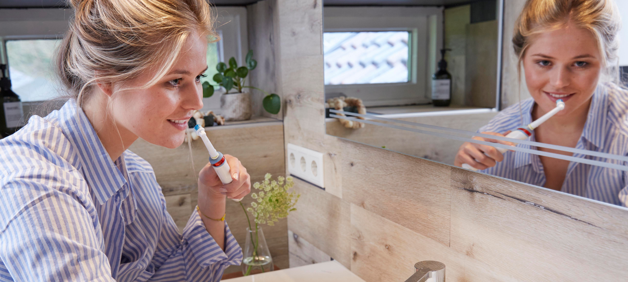 Woman in bathroom brushing teeth properly with bluem